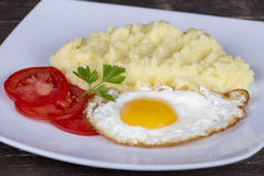 Mashed potatoes with fried eggs and tomato Royalty Free Stock Images