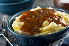 Mashed potatoes with gravy. A bowl of delicious mashed potatoes with gravy and melted butter royalty free stock image
