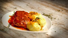 Mashed potatoes and meatballs with tomato sauce on white plate Stock Image