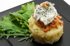 Mashed potatoes with shrimps and creamy cheese close-up. Mashed potatoes with shrimps and creamy cheese on a black plate close-up stock photos
