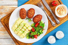 Mashed potatoes sprinkled with greens,  juicy meat cutlets Stock Images