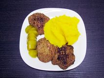 Mashed potatoes, patties and salted cucumber on a plate stock images