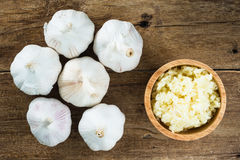 Mashed white garlic in wooden bowl with garlic cloves on wood table. Top view Royalty Free Stock Photos