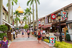 Masjid Sultan Mosque and Street. KAMPONG GLAM, SINGAPORE - AUGUST 17, 2016: Shops and restaurants in historic buildings fill the palm-tree-lined pedestrian Stock Photography