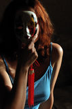 Mask. Girl with red hair behind a mask royalty free stock photography