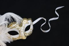 Mask. Gold and white venetian mask with feathers and white ribbon on a black background Stock Photography