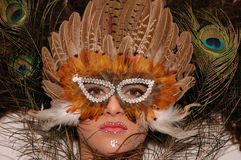 Mask. Girl wearing makeup made of rhinestone flowers with peacock feathers in her hair and mask in her face Stock Images
