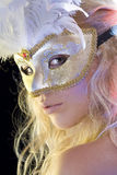 In mask. Close up portrait of young woman wearing mask on color back Royalty Free Stock Photography