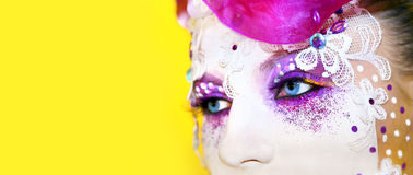 Mask. Makeup in the form of masks with eyelashes, rhinestone, accessories, silver glitter on a yellow background royalty free stock images