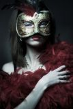 Mask. Portrait of attractive beautiful young woman wearing red-gold  carnival mask Royalty Free Stock Photography