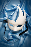 Mask. White carnival mask on blue silk Royalty Free Stock Images