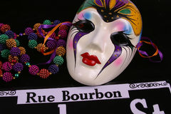 Mask, Beads and Rue Bourbon. Mardi Gras mask, beads and a Rue Bourbon sign on black background