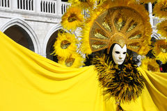 Mask in beautiful yellow costume at carnival in Venice Royalty Free Stock Photos