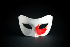 Mask On Black. Art concept. White mask with red spot of paint on black background