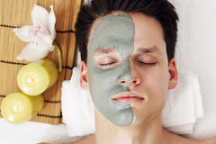 The mask of blue clay. Is applied with a brush to the man Royalty Free Stock Images