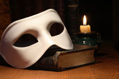 Mask On Book. Closeup of white venetian mask lying on vintage old book near lighting candle