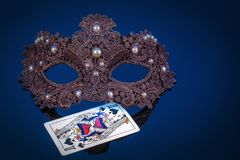 Mask. Carnival mask with pearls on a dark blue background with a playing card the Queen of Spades Royalty Free Stock Image