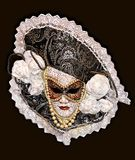 Mask on a dark gray background. Carnival mask decorated with beads and lace fabric, is shown on a dark background Royalty Free Stock Photography