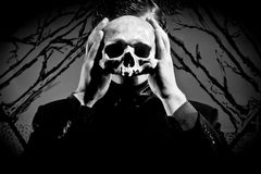 Mask of depression. A young man dressed in black with a skull in his hands. Black and white. Artistic background created by me Stock Photography