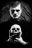 Mask of depression. A young man dressed in black with a skull in his hands. Black and white. Artistic background created by me Stock Photos