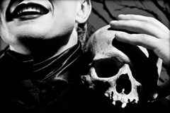 Mask of depression. A young man dressed in black with a skull in his hands. Black and white. Artistic background created by me Royalty Free Stock Photos