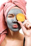 Mask for skin woman, happy and funny girl makes a mask for face skin, girl closes her eyes with orange and send an air kiss in stock images