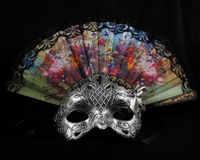Mask and fan. Silver carnival mask laying with folding fan on black fabric background front view Royalty Free Stock Photos