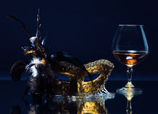 Mask with feather and brandy on a mirror table Stock Photography
