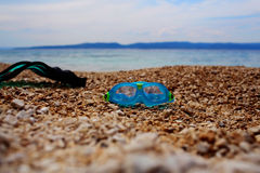 Mask and flipper. Mask goggles and flipper for diving snorkeling or swimming in sea on pebble beach on summer day over blue seascape stock photo