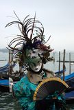 A mask with folding fan at the Venice carnival royalty free stock photography