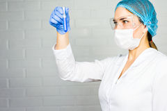 Mask and goggles protected life science researcher observing. Focus on scientist`s eye. Health care and biotechnology. Concept Stock Image