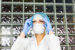 Mask and goggles protected life science researcher observing. Focus on scientist`s eye. Health care and biotechnology Royalty Free Stock Photo