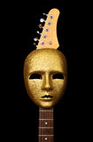 Mask and guitar. Guitar and gold mask. black background royalty free stock image