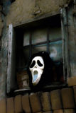 Mask. Hanging on the window of abandoned old farmhouse Stock Images
