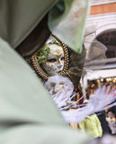 Mask in a Mirror. Venice, Italy-February 19, 2012: Image of the reflection in a mirror of a person in a specific Venetian mask during the Carnival days Royalty Free Stock Photos