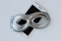 Mask on mobile phone - Concept of privacy, security and anonymity of mobile phones. Mask on mobile phone. Concept of privacy, security and anonymity of mobile stock photography