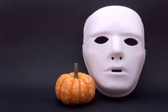 Mask and pumpkin. A white mask and a pumpkin on a black background, with plenty of room for copyspace Royalty Free Stock Images