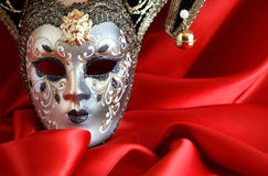 Mask On Red. Closeup of classical venetian mask on red silk background with free space for text