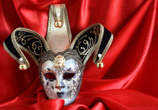 Mask On Red. Closeup of classical venetian mask on red silk background