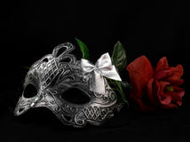Mask and rose. Silver carnival masks laying with red rose on black fabric background Royalty Free Stock Photography