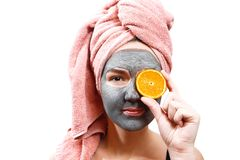 Mask for skin woman, happy and funny girl makes a mask for face skin, girl closes her eyes with orange, serious girl, royalty free stock photo