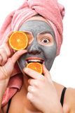 Mask for skin woman, happy and funny girl makes a mask for face skin, girl closes her eyes with orange, girl is smiling and bites royalty free stock images