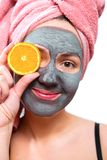 Mask for skin woman, happy and funny girl makes a mask for face skin, girl closes her eyes with orange, girl is smiling, stock photo