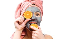 Mask for skin woman, happy and funny girl makes a mask for face skin, girl closes her eyes with orange, girl is smiling and bites royalty free stock photography