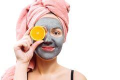 Mask for skin woman, happy and funny girl makes a mask for face skin, girl closes her eyes with orange, girl is smiling, stock images
