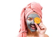 Mask for skin woman, happy and funny girl makes a mask for face skin, girl closes her eyes with orange, photo royalty free stock images