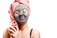 Mask for skin woman, happy girl holding a towel, girl enjoys a mask for face skin, closed eyes with pleasure stock photography