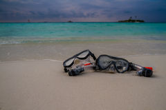 Mask and snorkel lying on sandy beach. Sea waves background. Stock Images