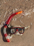 Mask and snorkel lying on wet sand with waves Stock Photo