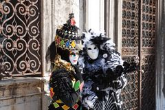 The two carnival costumes near the iron gates. stock photos